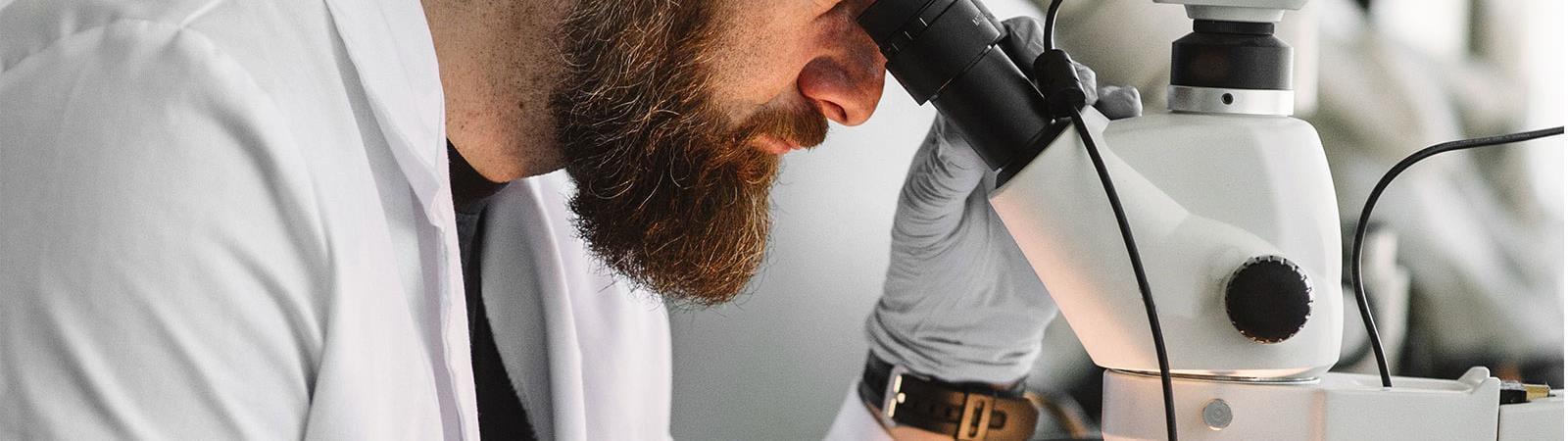 Homme regardant dans le microscope